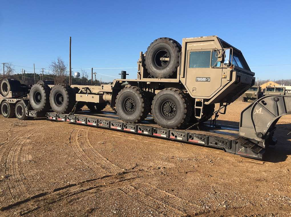 tactical vehicle on top of flatbed trailer outdoors