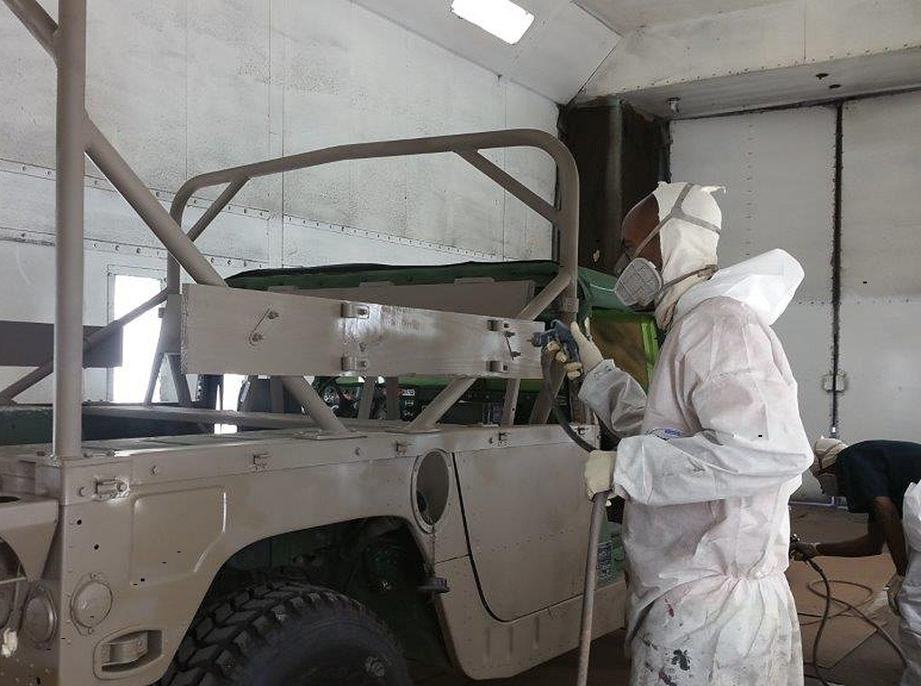 worker wearing PPE painting tactical vehicle with paint gun