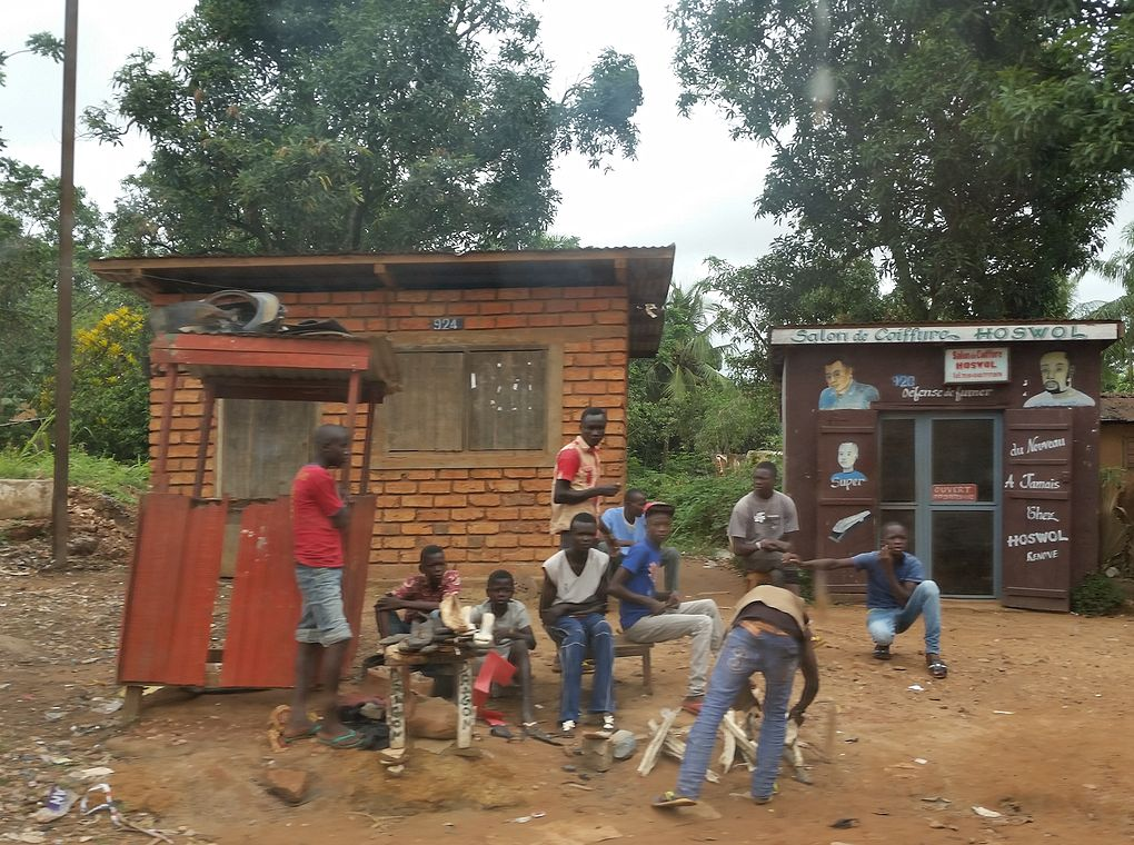 group of young people gathered outside two small buildings