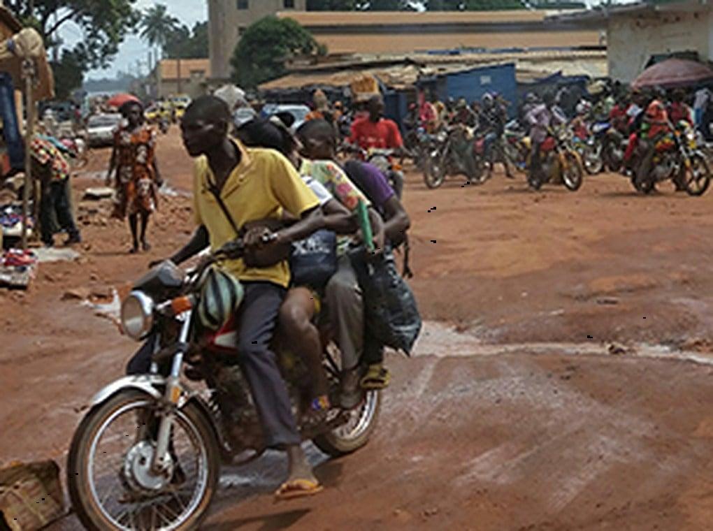 people riding motorbikes through village