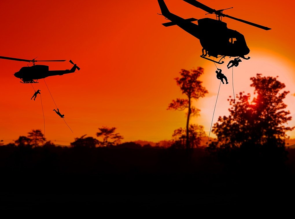 soldiers descending from helicopters at sundown