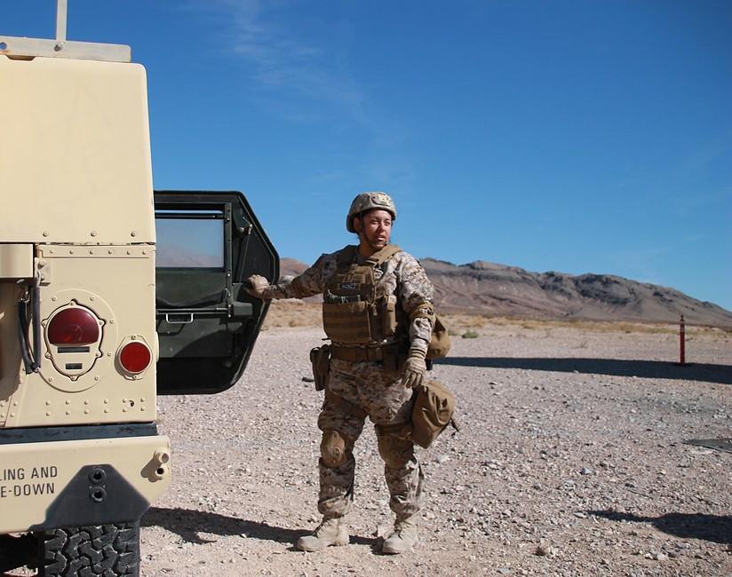 female soldier by Humvee
